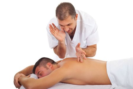 masseur: Real professional masseur massaging  back of young man at spa salon