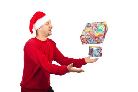 Happy man wearing Santa helper and trying to catch Christmas gifts in motion isolated on white backgroud photo
