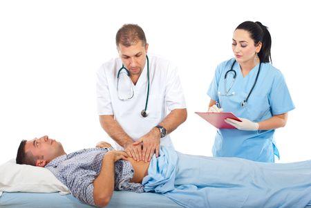 dolor de estomago: Doctor palpar con su manos enfermos masculinos paciente abdomen y una enfermera tomando notas en un Portapapeles en el hospital