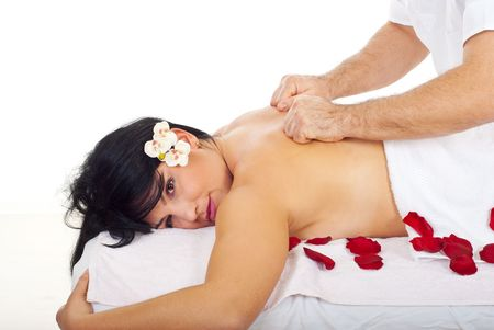 Pretty woman with orchid flower receiving a deep back massage at spa resort photo