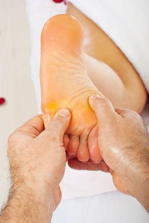Close up of mans hands massaging womans foot photo