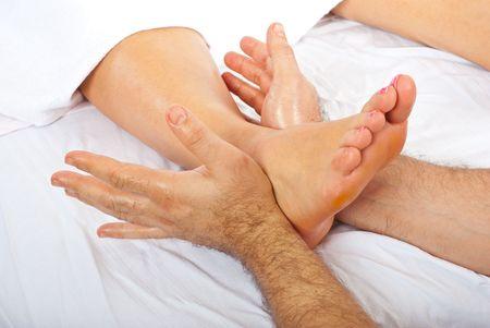 Detail of mans hands massaging womans foot at spa resort photo
