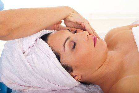 Cute woman receiving facial massage at spa salon photo