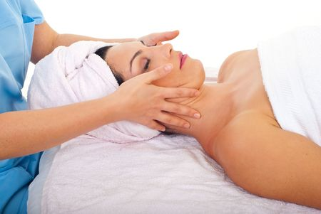 Beautiful woman relaxing with a facial massage at spa retreat photo