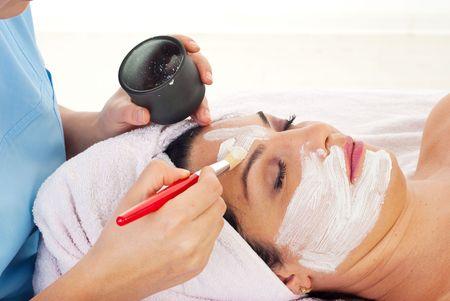 Close up of beautician applying facial mask to a woman at spa salon photo
