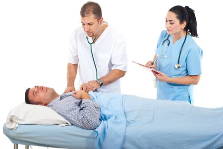 assessing: Physician man assessing sick patient in hospital and a nurse assisting them isolated on white background