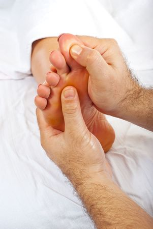 Close up of health worker hands give reflexology massage to woman foot photo