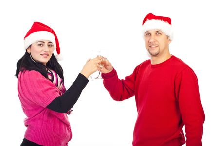 Happy festive couple wearing santa hats and toasting with champagne celebrating Christmas night isolated on white background photo