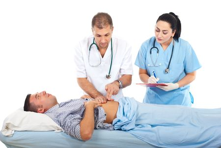 stomachache woman: Doctor palpate patient man abdomen while other doctor aking notes in clipboard in hospital
