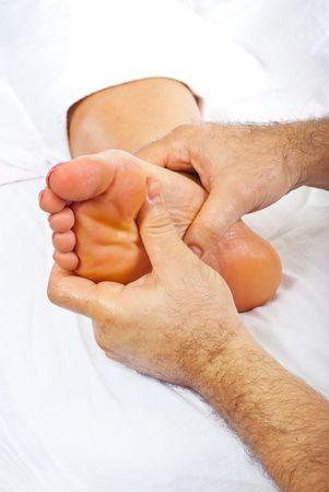 pies masculinos: Masajista profesional dando masaje de reflexolog�a a pie de la mujer  Foto de archivo