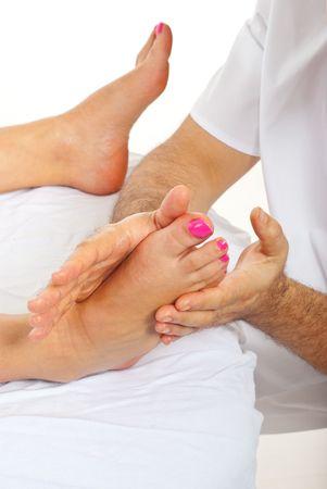 Masseur man massaging woman feet and making pressure at spa salon photo