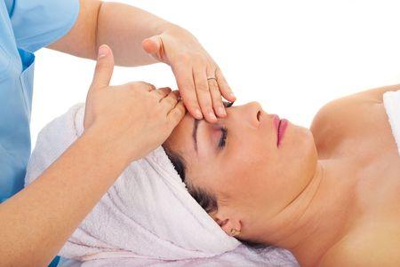 Beautician giving facial massage to a beautiful woman at spa resort photo