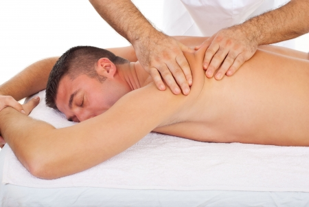 therapeutic massage: Professional masseur kneading man back skin at massage in a spa salon