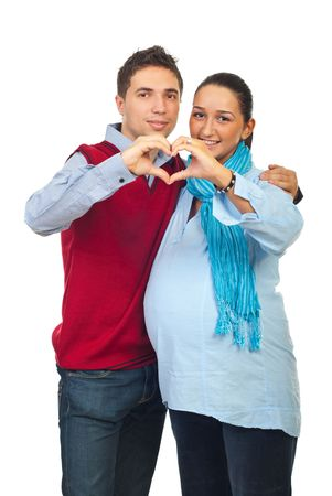 Couple with pregnant woman   forming a heart with their hands  to show love isolated on white background photo