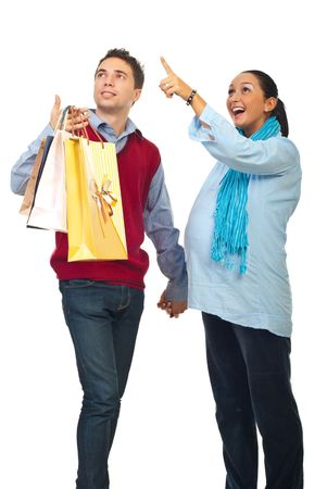 Surprised pregnant woman pointing up and her husband being amazed and holding shopping bags isolated on white background photo
