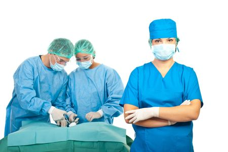 Surgeon woman with mask and protective clothes standing with hands crossed in front of image while her team arrange surgical tools on table and preparing for operation photo