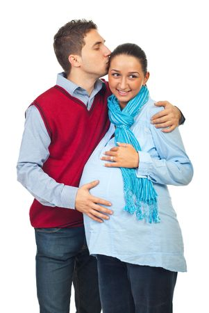 Husband giving a soft  kiss on forehead pregnant wife and holding his hand on belly isolated on white background photo