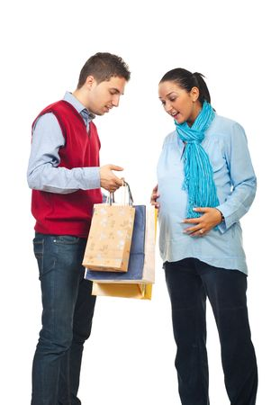 Man showing to his pregnant wife  inside of shopping bags and the woman being surprised and happy  isolated on white background photo