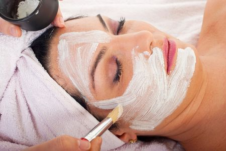 Close up of hand applying facial mask to woman face at  beauty salon photo