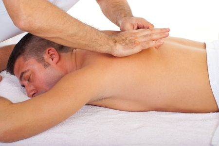 back massage: Man relaxing with a back massage at spa retreat