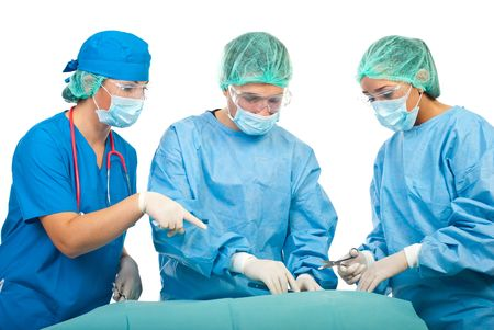 Three surgeons operating in operation room,a surgeon woman showing something to her collegue photo