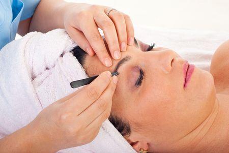 cejas: Close up de manos de esteticista desplumado cejas de mujer en un retiro de spa