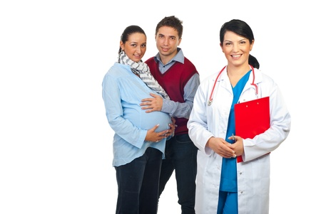 Friendly doctor with clipboard in front of image smiling and a  pregant woman with her husband standing in background,selective focus on couple photo