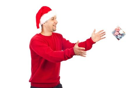 Happy Santa helper man with beard trying to catch a small gift in motion isolated on white background photo