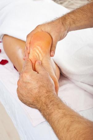 Masseur giving reflexology massage to woman feet photo
