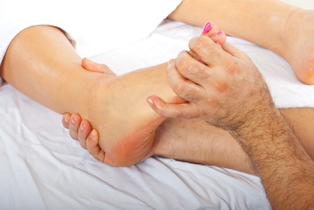 Health care worker giving orthopedic massage to woman feet photo