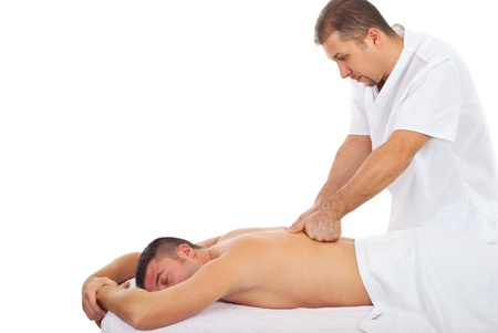 therapeutic massage: Real professional masseur giving deep back massage to a man in a spa resort