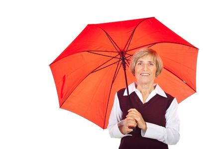Smiling senior woman holding a red umbrella isolated on white background photo