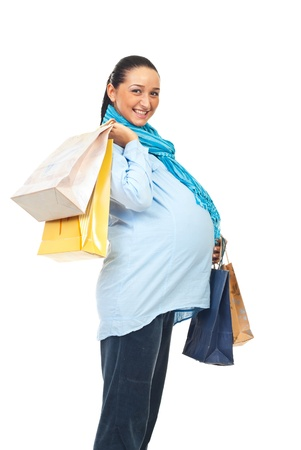 Profile of beautiful happy pregnant woman holding shopping bags isolated on white background photo