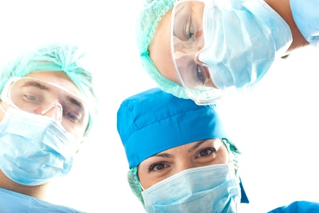 surgical tool: Bottom view of three heads on surgeons in operation Stock Photo