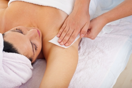 depilation: Close up of woman getting waxing armpit by beautician in a beauty salon