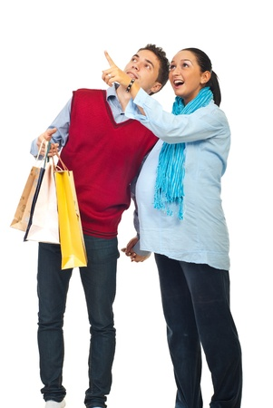 Happy couple at shopping ,pregnant wife showing something to her husband and pointing up isolated on white background photo