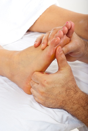 Detail of man hands doing reflexology massage to woman feet photo