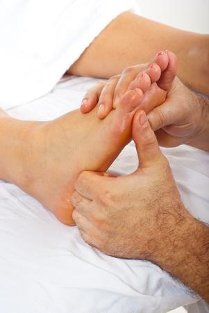 Detail of man hands doing reflexology massage to woman feet photo