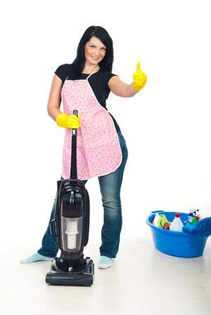Smiling cleaning woman with pink apron holding a vacuum cleaner and giving thumb up  Stock Photo