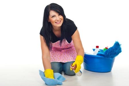 mujer limpiando: Feliz mujer de limpieza arrodillarse y piso barrido con un pa�o de dustt y el spray en su casa