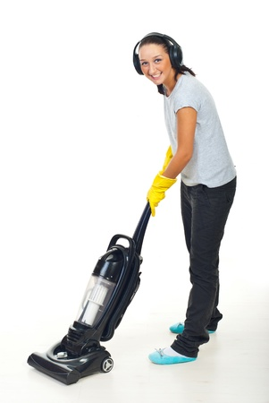 gloves women: Happy woman listening music in headphones and working with vacuum cleaner on white wooden floor