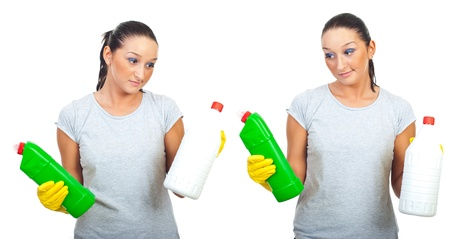 Woman  with grimace on face trying to choice from two cleaning products isolated on white background photo