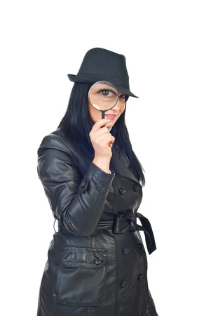 Detective woman in black hat and leather jacket holding a magnifying glass to eye isolated on white background photo