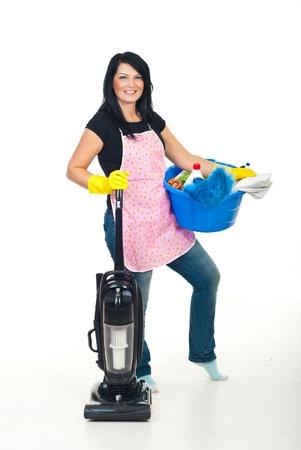 schoonmaakartikelen: Vrolijke vrouw met roze schort voorbereiding voor het reinigen van huis met stofzuiger en houden een blauwe tafel met reinigings producten