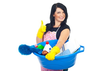 Woman holding a basin with brush and cleaning products and giving thumbs up with hands in gloves photo