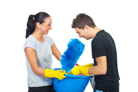Laughing couple having fun and holding cleaning products for house isolated on white background photo