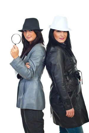 Two beautiful detectives women standing back to back and wearing hats and leather jackets  isolated on white background photo