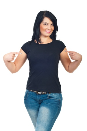 Attractive brunette woman  pointing with both fingers to her blank black t-shirt isolated on white background