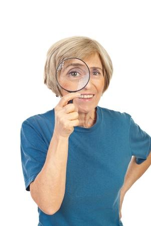 glass eye: Senior mujer mirando a trav�s de la lupa y sonriente aislado sobre fondo blanco