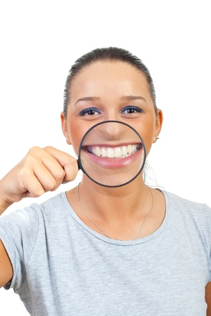 perfect teeth: Funny young woman using magnifying glass to enlarge her smile isolated on white background